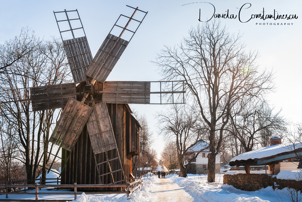 Windmill on a snow covered street at the Village Museum in Bucharest